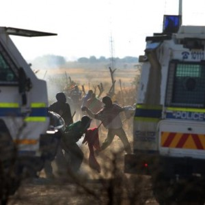 Sticks and stones versus bullets: Miners can be seen between police vehicles throwing rocks at officers. Victims on both sides have been killed in recent days